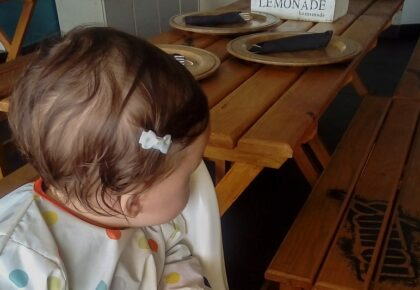 Little girl in a high chair at a restaurant in Portugal. Family holidays to Portugal