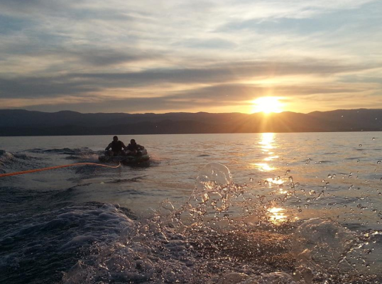 Two on a tube being towed by an unseen boat, with sun setting over the mountains behind Bear Lake.