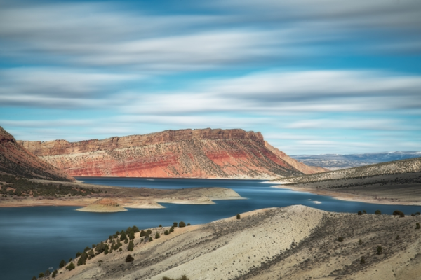Vermilion bluff speckled with junipers thrusting out of a dark teal lake.