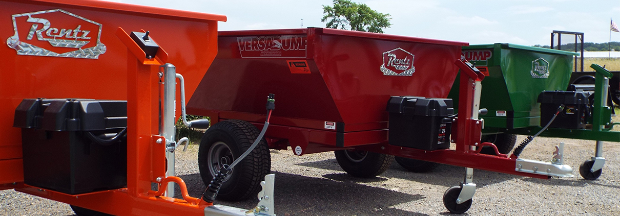 Trio of mini-dump trailers in orange, red, and green.