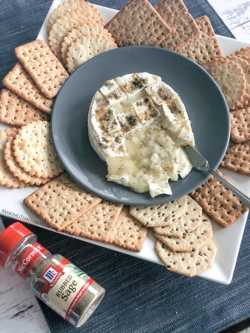 Gooey Garlic Sage Baked Brie oozing on a plate with crackers for dipping