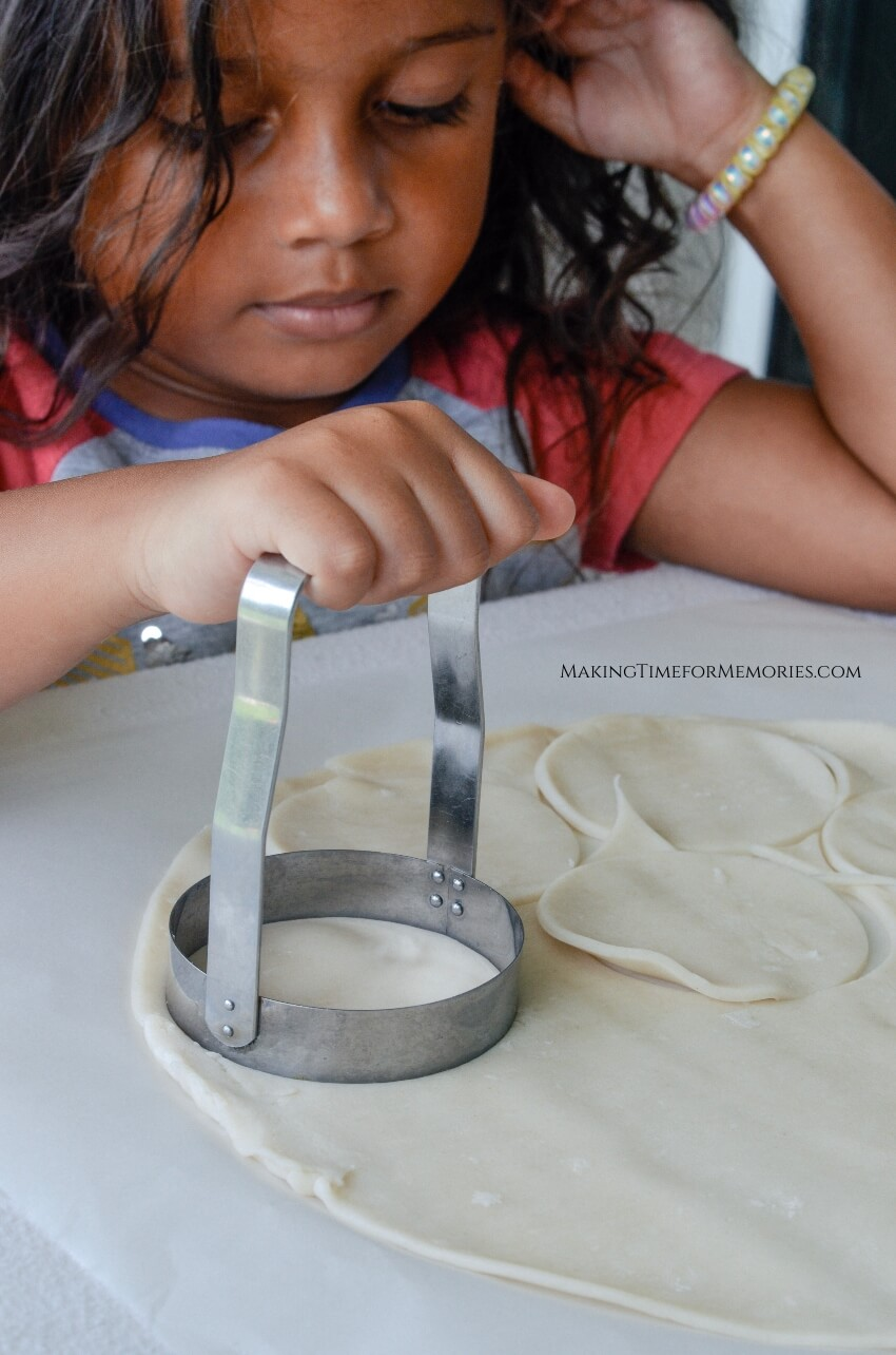 little girl using round biscuit cutter to cut dough rounds