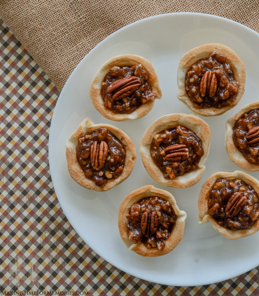 mini pecan pies displayed on a plate with fall colored linens