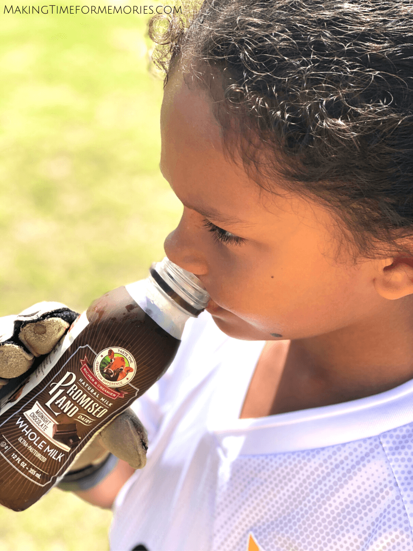 young boy in white soccer uniform and wearing goalie gloves, drinking chocolate whole milk on a soccer field
