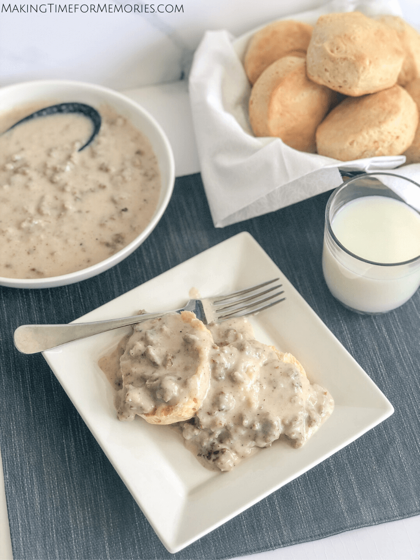 table setting with a big bowl of homemade sausage gravy, a bowl of fresh out of the oven biscuits, a glass of milk, and a square white plate featuring an open biscuit smothered with gravy