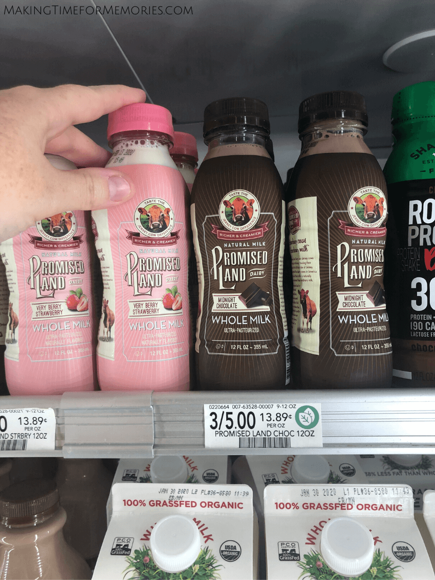 adult hand reaching for Promised Land 12 oz. chocolate and strawberry whole milk on a refrigerated shelf in a store