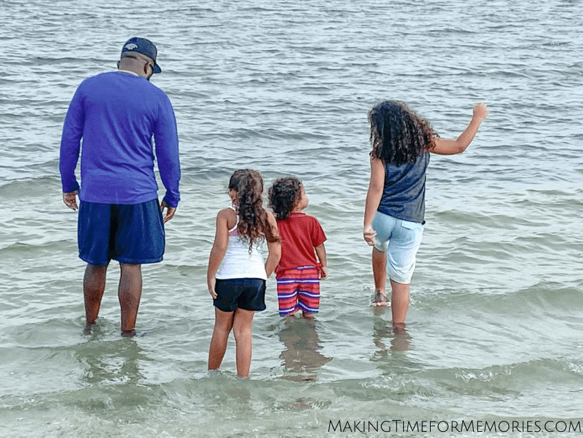family standing in the water along the Sanibel Causeway
