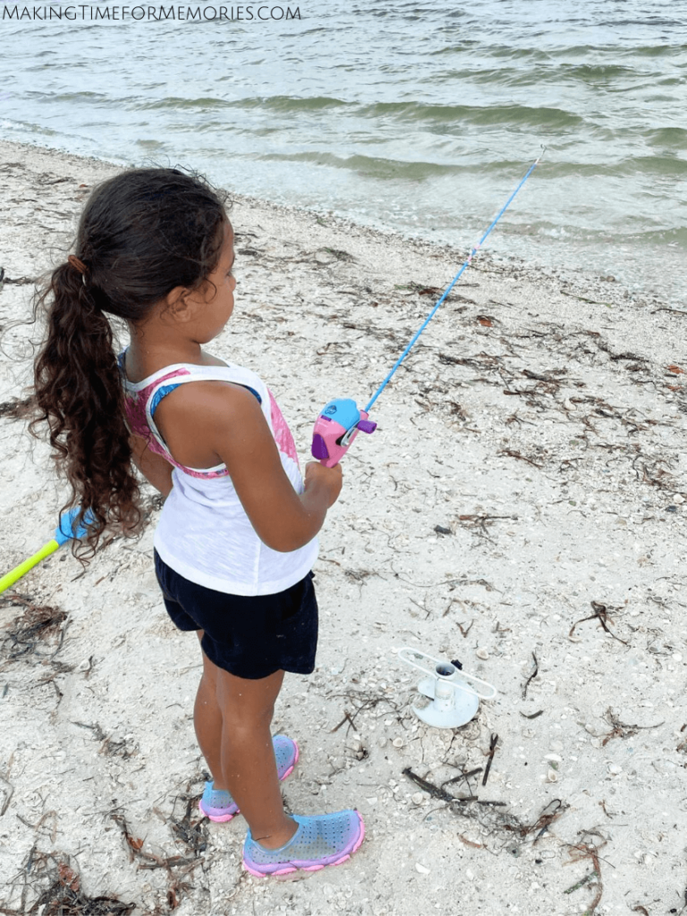 girl fishing the Sanibel Causeway and wearing her beach shoes to prevent cutting her feet on the shells