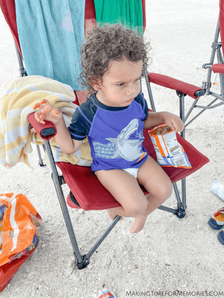 toddler enjoying a snack while sitting in a beach chair