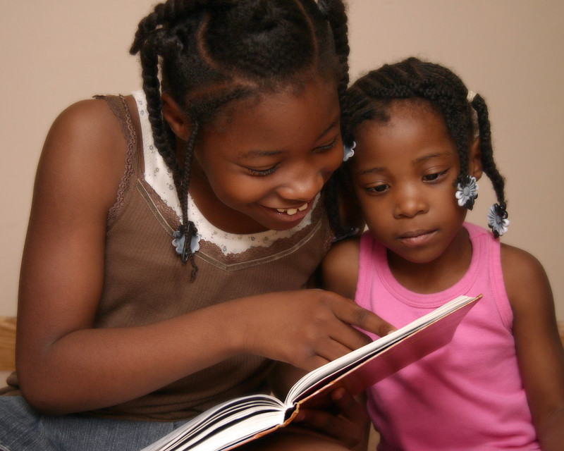 girl reading to her little sister