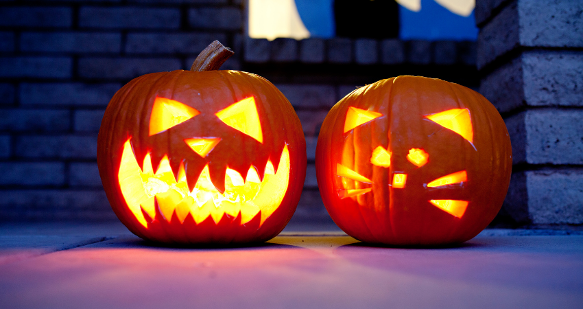 2 carved pumpkins, 1 jack-o-lantern face and 1 cat design