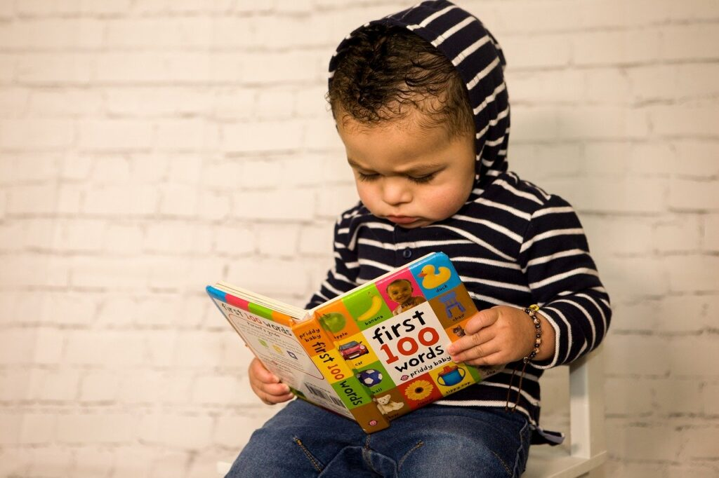 "toddler reading ""First 100 Words"" book from Priddy Books"