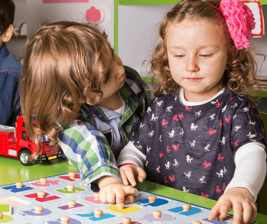 preschool boy and girl playing with a wooden alphabet peg puzzle