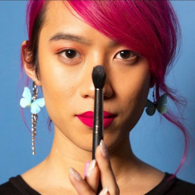 Gender expansive person with makeup brush