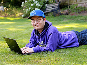 college student on lawn with laptop computer