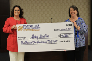Mary Brainerd (right) accepting Five Stone's donation from Joni Green (left) of behalf of Mercy.