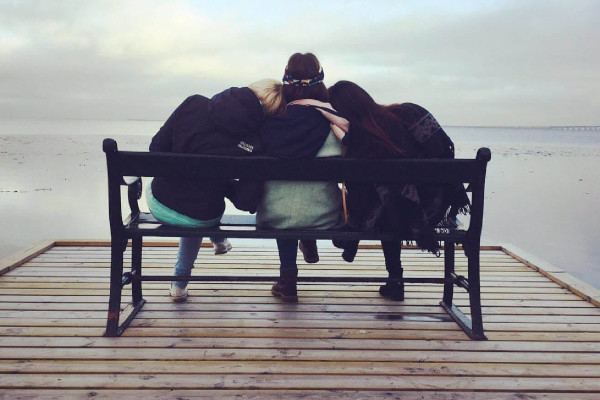 3 women sitting on a bench supporting each other - support a friend or loved one with depression