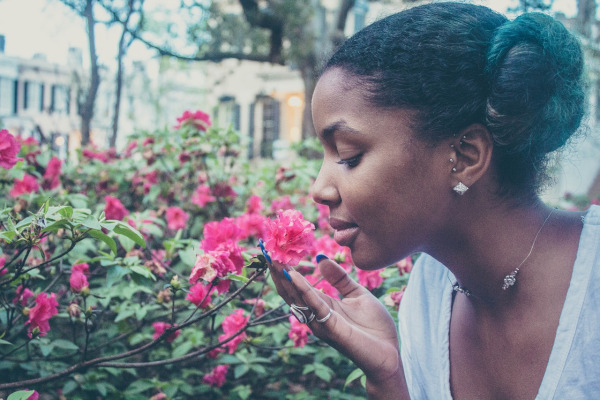 Girl smelling flowers, connecting with God in nature