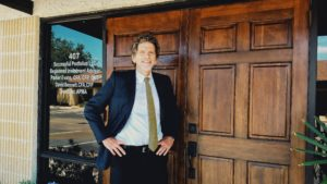 Parker Evans,CFA, CFP standing at front door of Successful Portfolios Office.