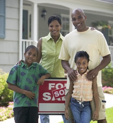 """Family Standing with House's """"For Sale"""" Sign"""