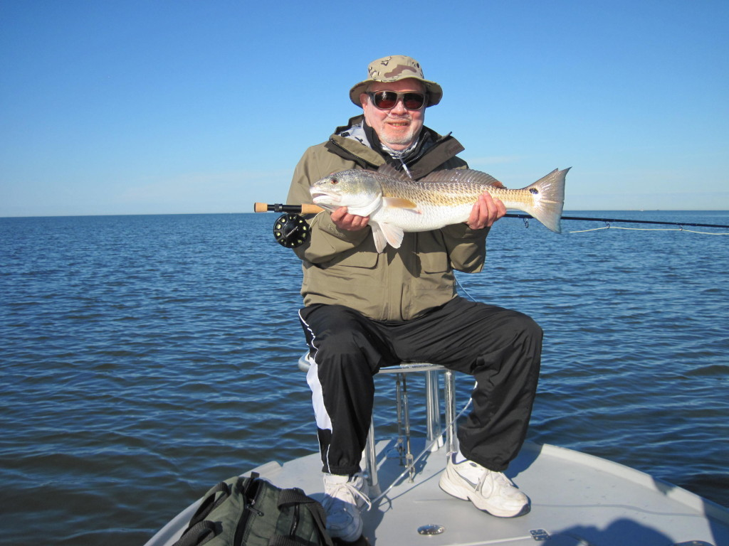 Holding the redfish (note the olive green bag on the deck that holds my size D oxygen cylinder)