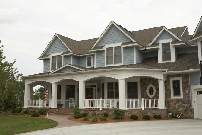 elegant-traditional-home-exterior-blue-shaker-siding-patriotic-columns-stone-transom