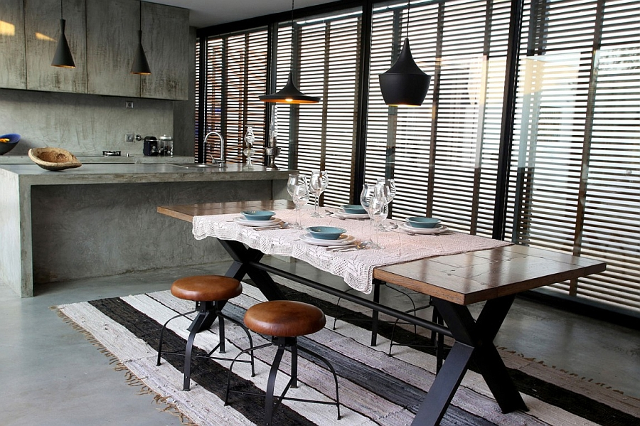 modern-industrial-styled-kitchen-with-dining-area-contains-wooden-dining-table-chic-stools-and-black-pendant-lights