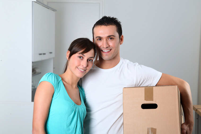 Young couple carrying boxes into new house