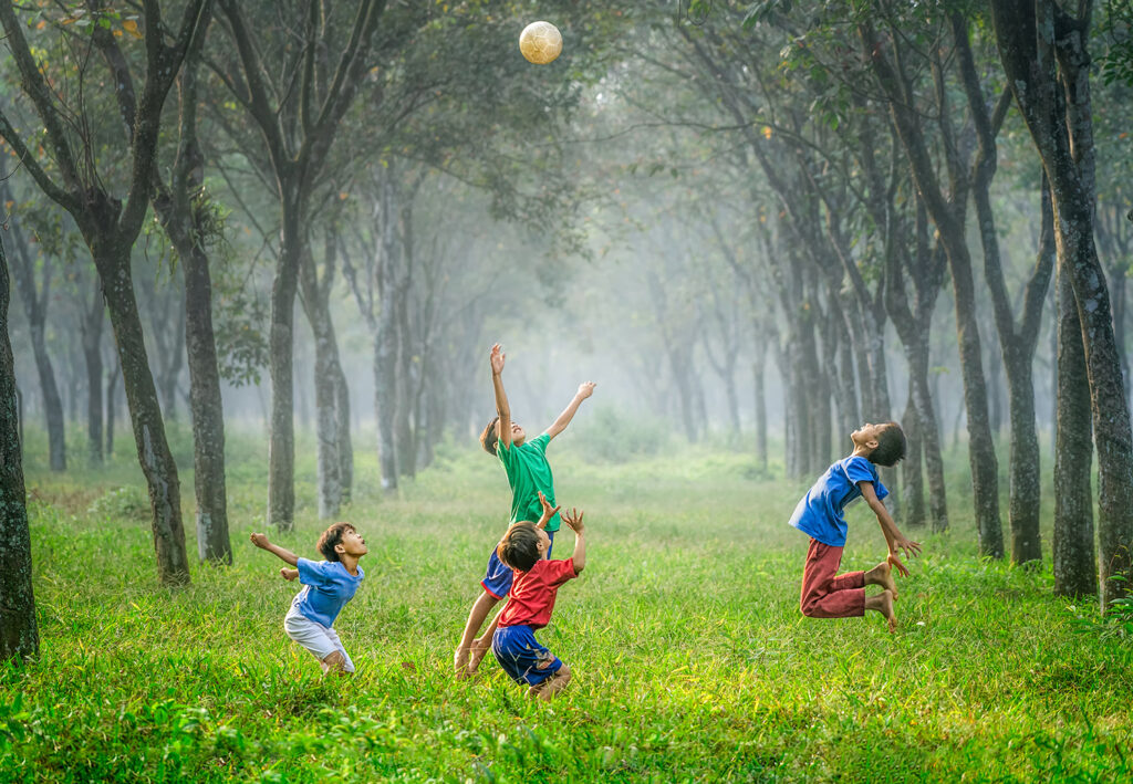 Boys playing soccer in field