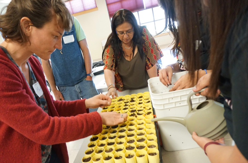 Meghan Collins (NWAL Education Lead) and Mary Rose Morigeau (Confederated Salish and Kootenai Tribes) learn native seed planting techniques from students from the Arlee EAGLES Club at NWAL Youth Day, Salish Kootenai College. May 3, 2018.