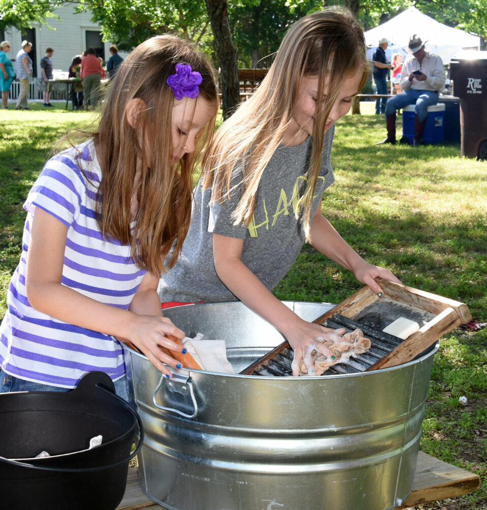 Two girls washing clothes in washtub