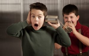 Image of two boys using a phone made of tin cans to be heard through