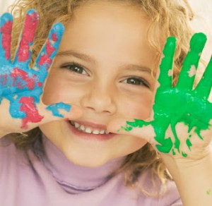 Smiling Girl with Hands Covered in Paint --- Image by © Royalty-Free/Corbis