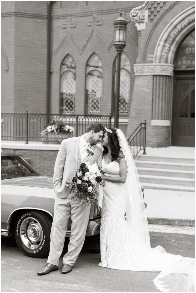bride and groom pose with Monte Carlo in front of a cathedral | Iowa wedding photographer | CB Studio