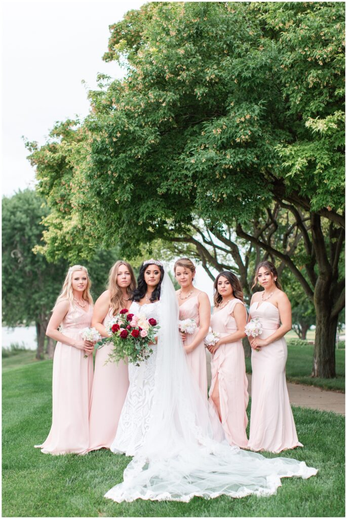 Bride wearing a cathedral length veil and crown and bridesmaids wearing blush pink gowns | Iowa wedding photographer | CB Studio