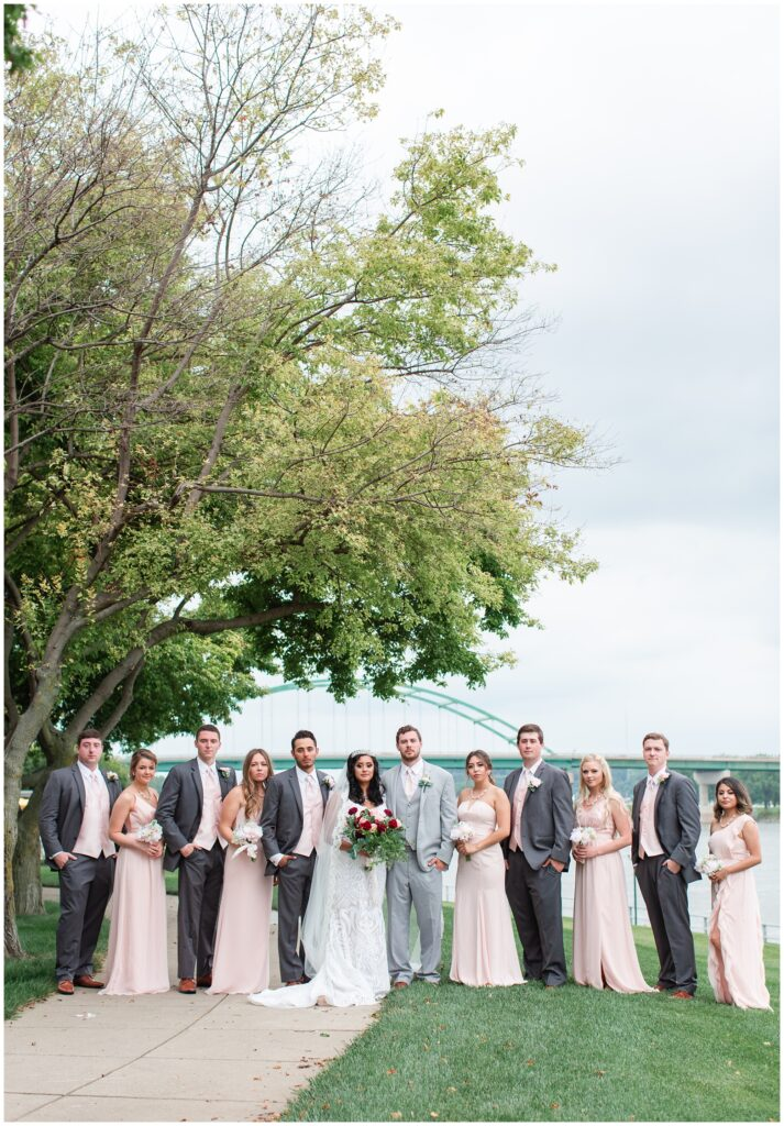 wedding party by the Sioux City bridge wearing blush pink gowns and grey tuxs | Iowa wedding photographer | CB Studio