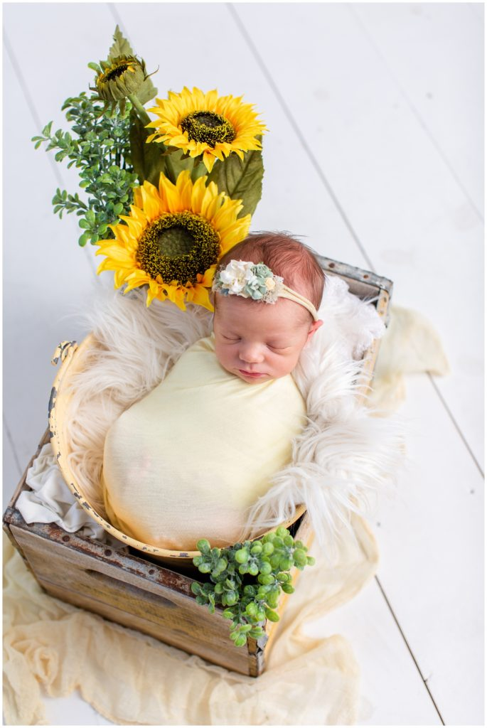 Newborn wrap posed in a yellow rustic bucket and box wearing a yellow wrap with sunflower, flotaki blanket and white details | Iowa Newborn Photographer | CB Studio