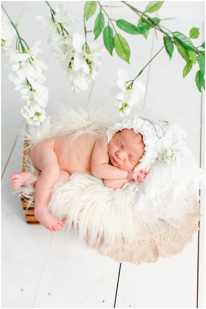 Newborn posed in a rustic box wearing a white lace bonnet with a lace pillow, flotaki blanket and white flower details | Iowa Newborn Photographer | CB Studio