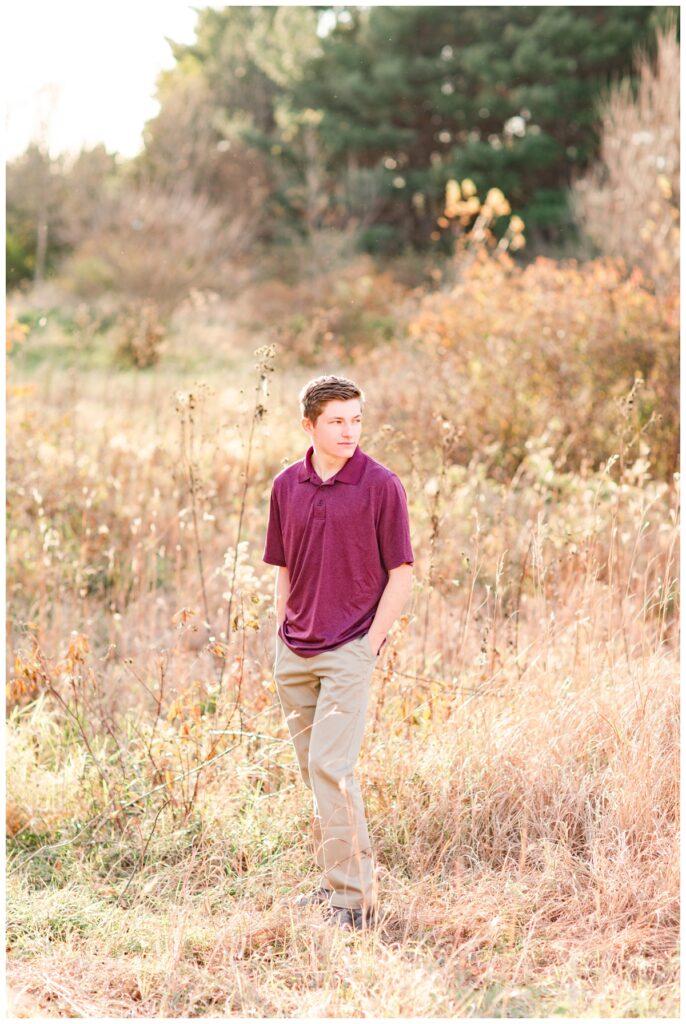 Fall senior boy session standing in a grassy field   Iowa Senior Photographer   CB Studio
