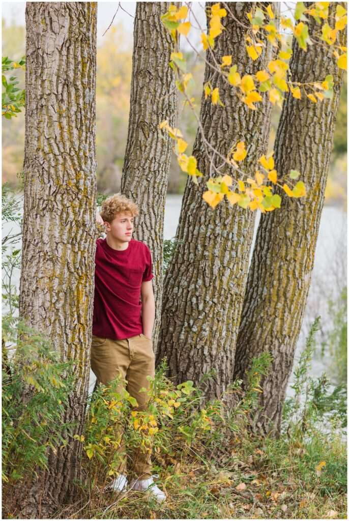 Senior boy leaning on a tree surrounded by fall foliage with a lake in the background at Plum Creek Wildlife Area | Iowa Senior Photographer | CB Studio