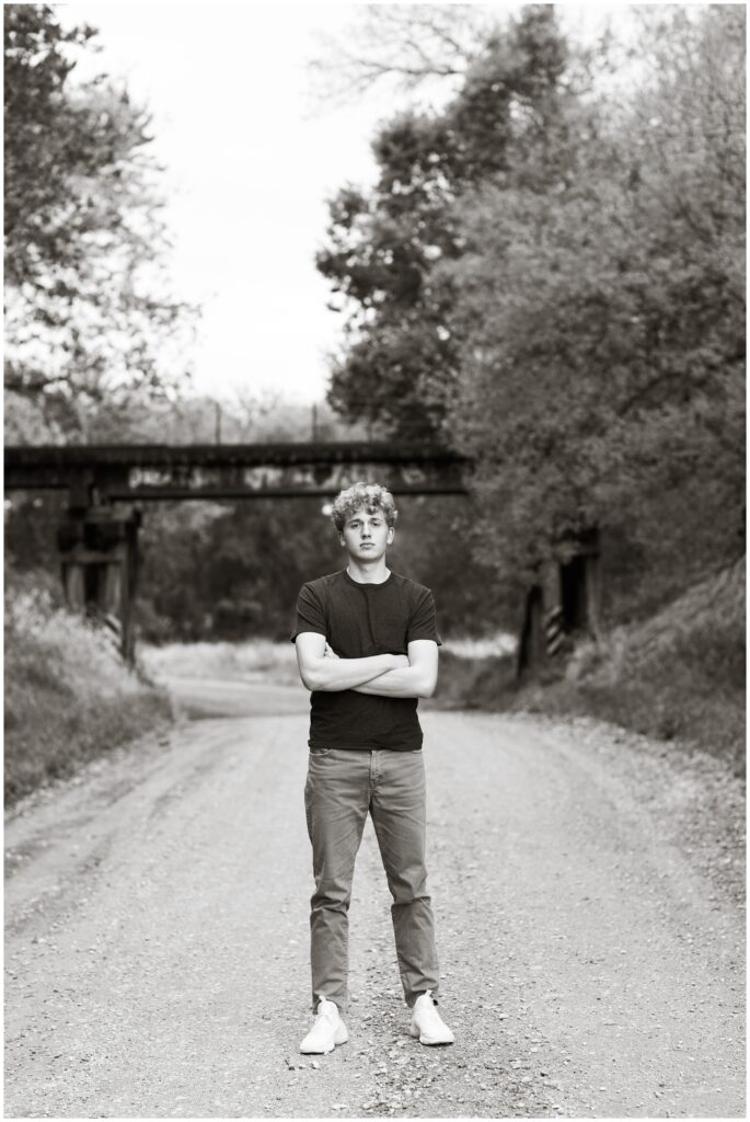 Senior boy standing on a gravel road in front of an old railroad bridge at Plum Creek Wildlife Area | Iowa Senior Photographer | CB Studio