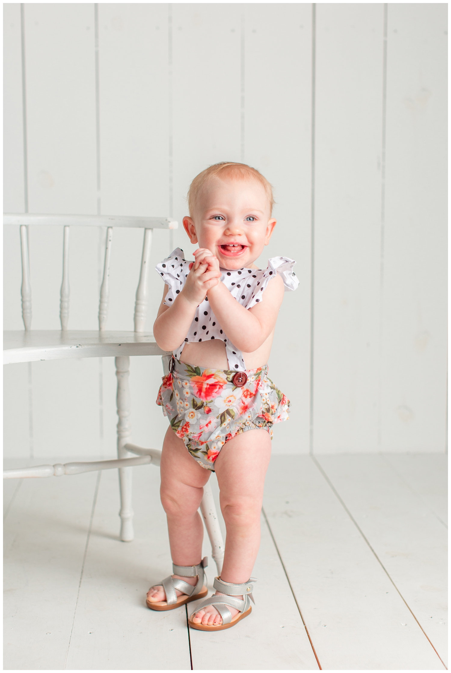 One year old baby girl standing on a white wood background wearing a floral and polka dot romper, smiling and clasping her hands | Iowa Baby Photographer | CB Studio