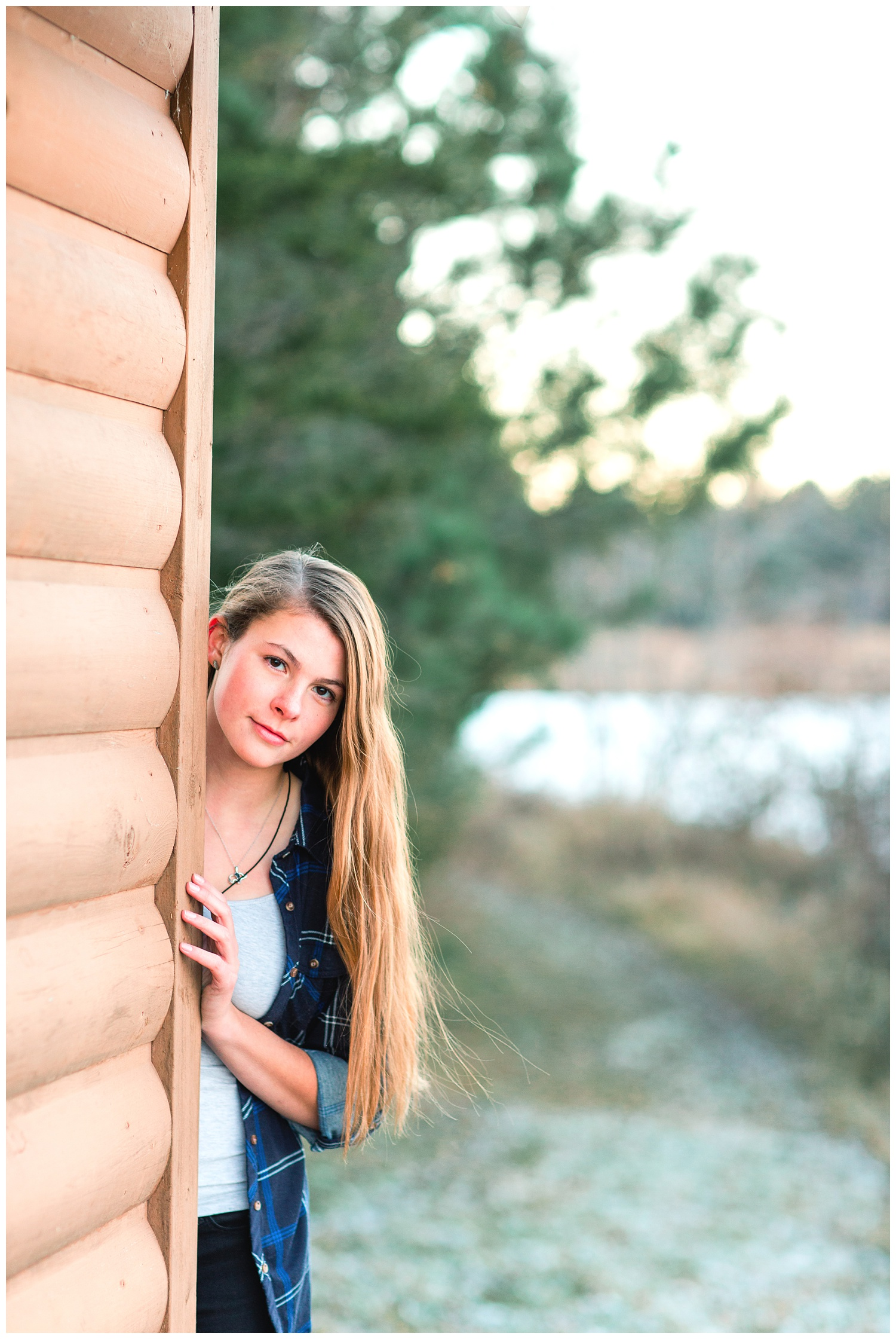 Senior girl peeking out from behind a wood building in a park with a lake during the fall | Iowa Senior Photographer | CB Studio