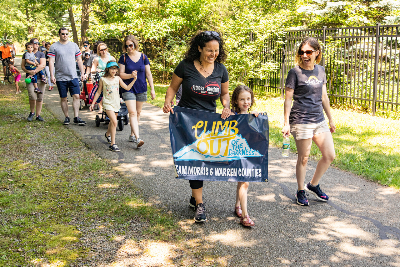 """Laura, Her Daughter Avery and Others Walking with the """"Climb Out of the Darkness"""" Banner"""