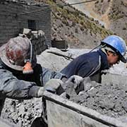 Young miners wearing helmets push rail carts filled with ore at a Bolivian mine.