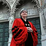 A woman wearing a red and black liturgical vestment, stands outside the majestic Cathedral of St. John the Divine in New York City.