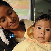 A young mother holds her 8-month-old wide-eyed daughter at a Guatemalan health clinic.