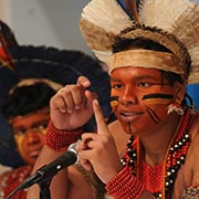 Indigenous adolescent boy wearing black and red face paint and traditional headdress and beads.