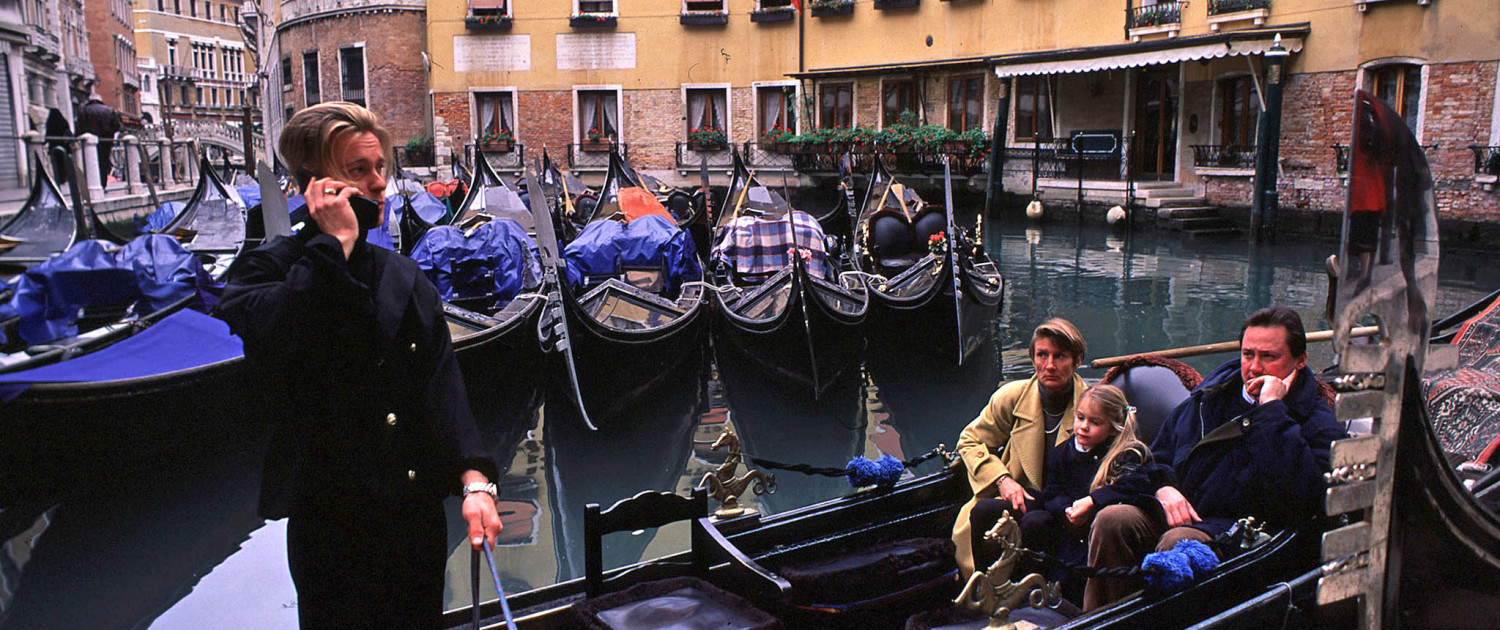 A family waits for a ride in a gondola as the gondolier takes a call on his mobile phone in Venice, Italy.