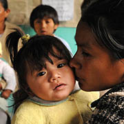 A woman tenderly kisses her infant daughter at a health center in Guatemala.
